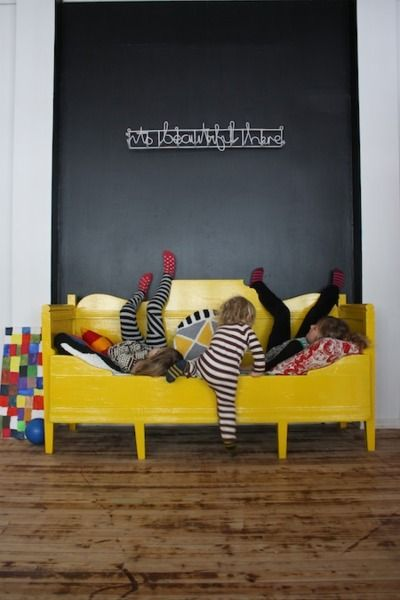 yellow daybed against black wall