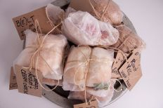 Picnic parcels, full of organic food, including homemade sandwiches packaged in parchment paper and twine.