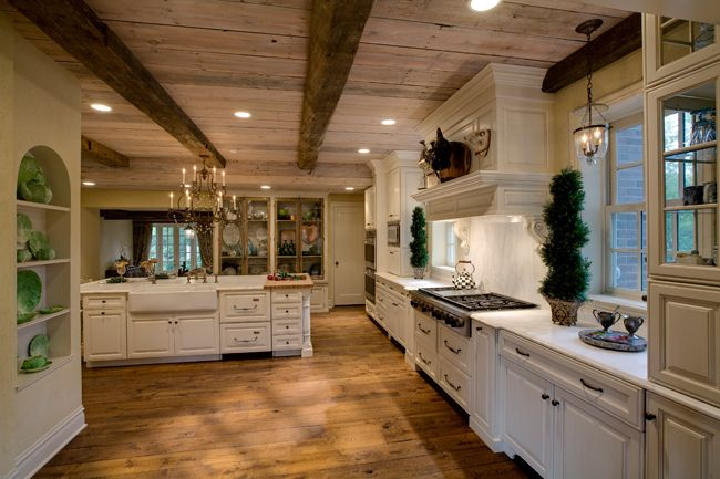 mantle hood, pine floors and old world style lighting in this kitchen make it look like an olde english countryside kitchen