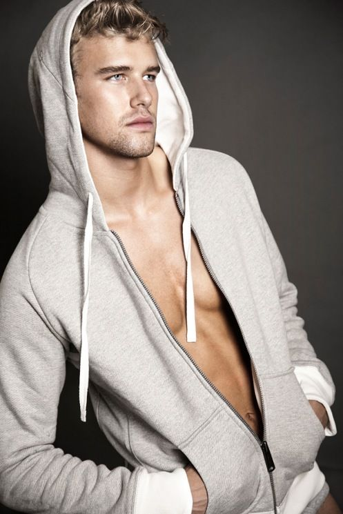 Young blonde male model wearing light grey hoodie.