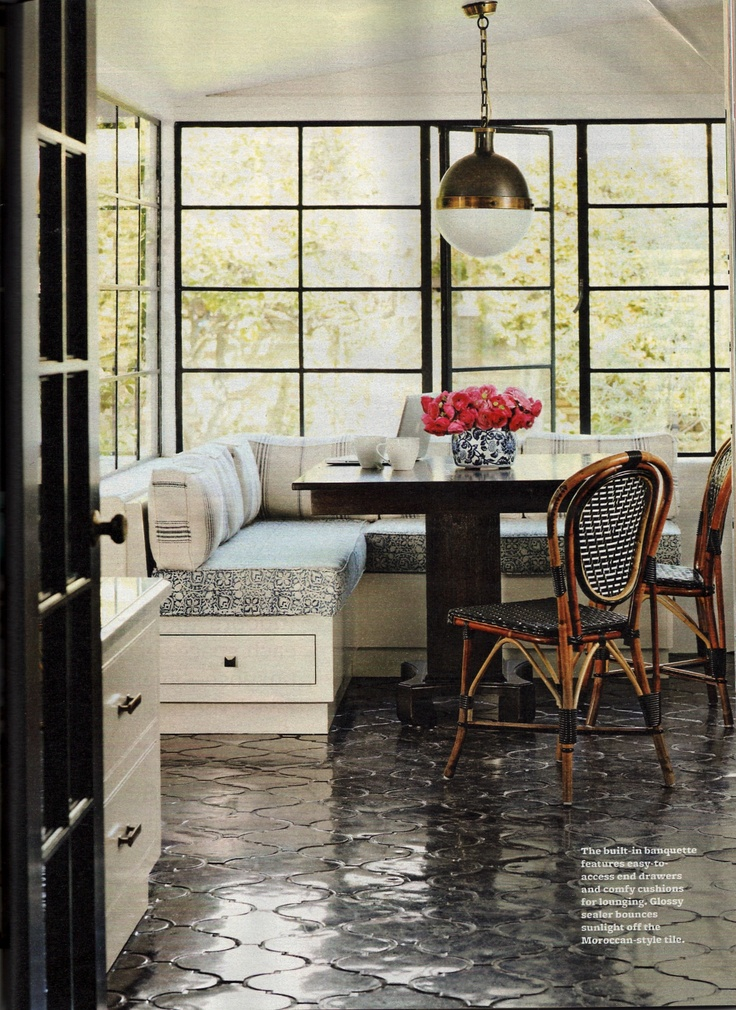 Glossy black morrocan tile flooring, rattan chairs, circa pendant light, vintage paned windows, cozy banquette.  Gorgeous!  BHG