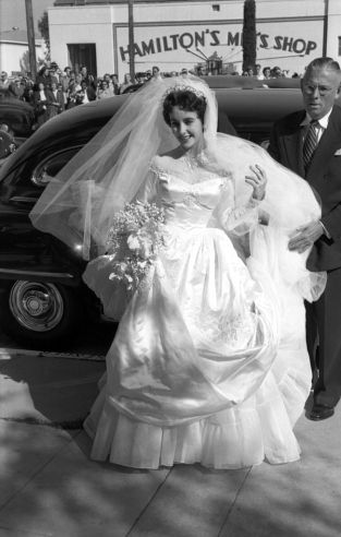 "Unpublished. Just 18 years old, Elizabeth Taylor arrives to marry hotel heir Conrad ""Nicky"" Hilton at the Bel-Air Country Club. This was the first of her eight marriages, and for the occasion she wore a gown given to her by MGM Studios"