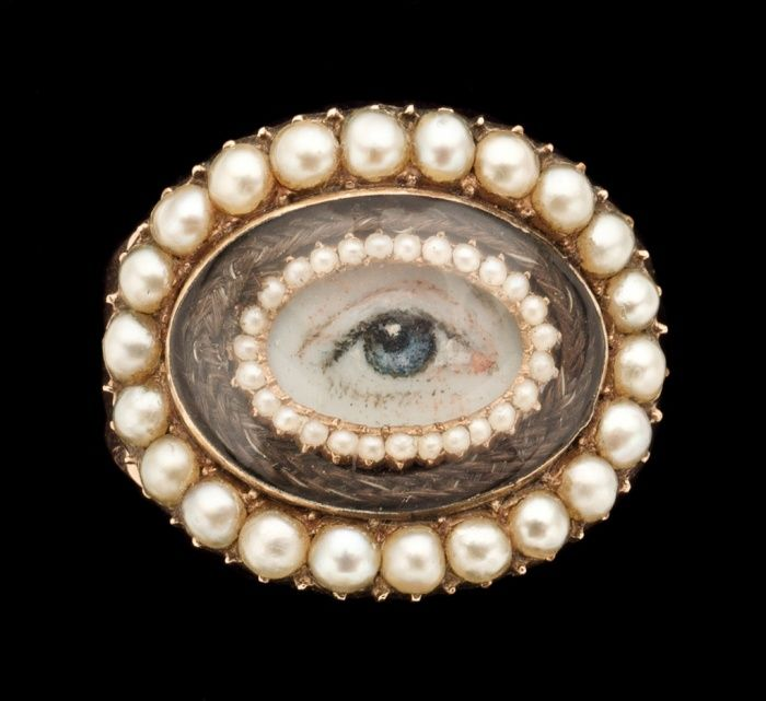 Gold ring set with an eye miniature within a border of seed pearls, plaited hair and half pearls from around 1810.