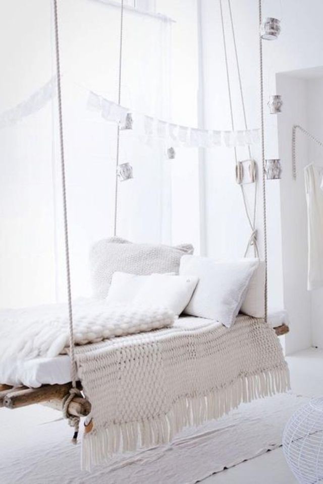 rustic hanging bed with white pillows and blankets