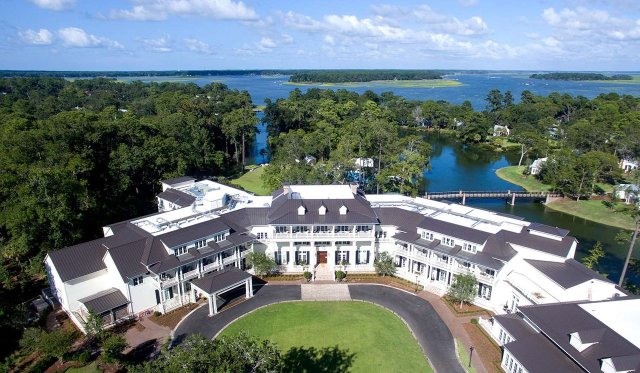 """Bâtiments blancs en U de 3 étages d'un complexe surplombant les lacs et les jardins. """"Width ="""" 1280 """"height ="""" 746"""