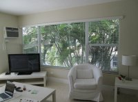 Living room with 2 large windows overlooking the pool and ...