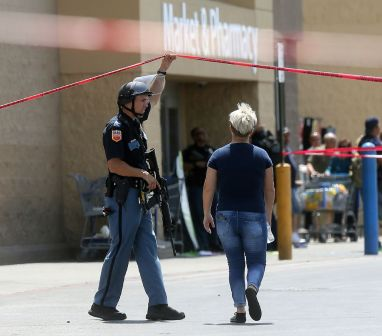 An employee crosses into the crime scene following a shooting at a Walmart in El Paso, Texas, Saturday, Aug. 3, 2019. (Mark Lambie/The El Paso Times via AP)