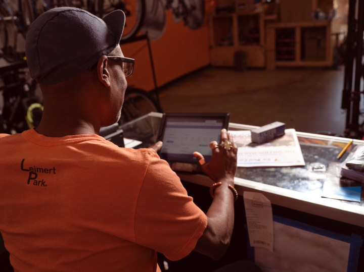 Adé sits at the front desk of the bike shop, with an iPad open on a PayPal seller page.