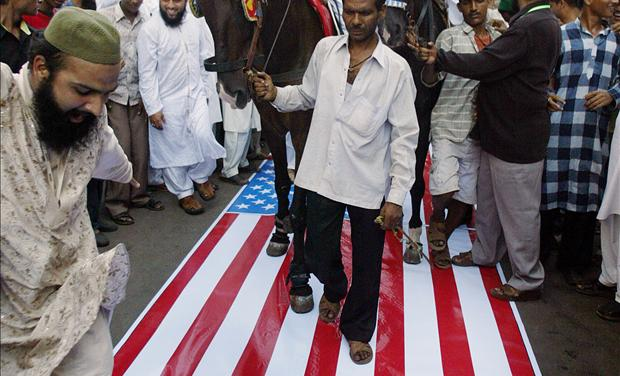 Indian Muslims shout anti-US slogans as they ride horses over the U.S. flag during a demonstration
