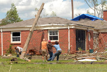 Unnamed residents lend a hand removing a tree from a house.