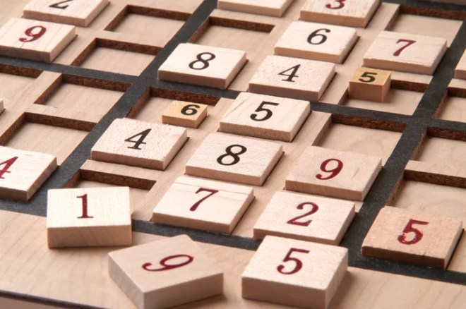 A photograph of a wooden Sudoku puzzle board with numbers askew and out of order