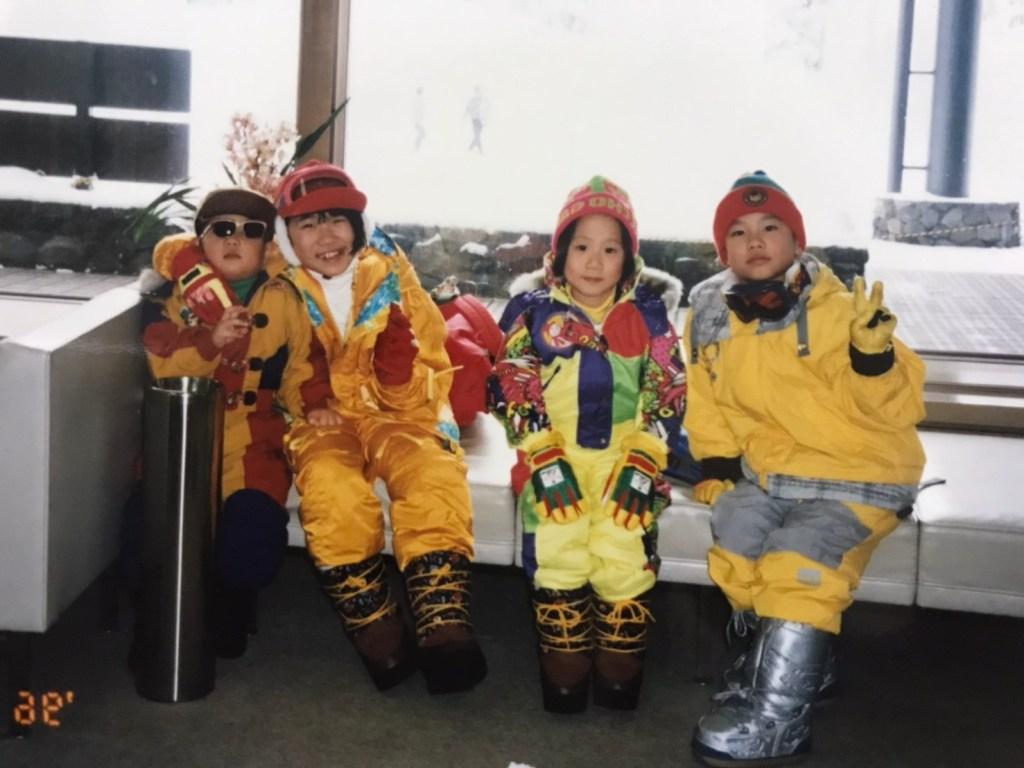 スキー場の室内で並んで座る4人兄妹