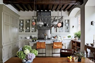 kitchen pot racks faucets review the ultimate in chic organization architectural display her sophisticated london conceived by michael s smith an ann morris rack light fixture hangs above stools lucca antiques