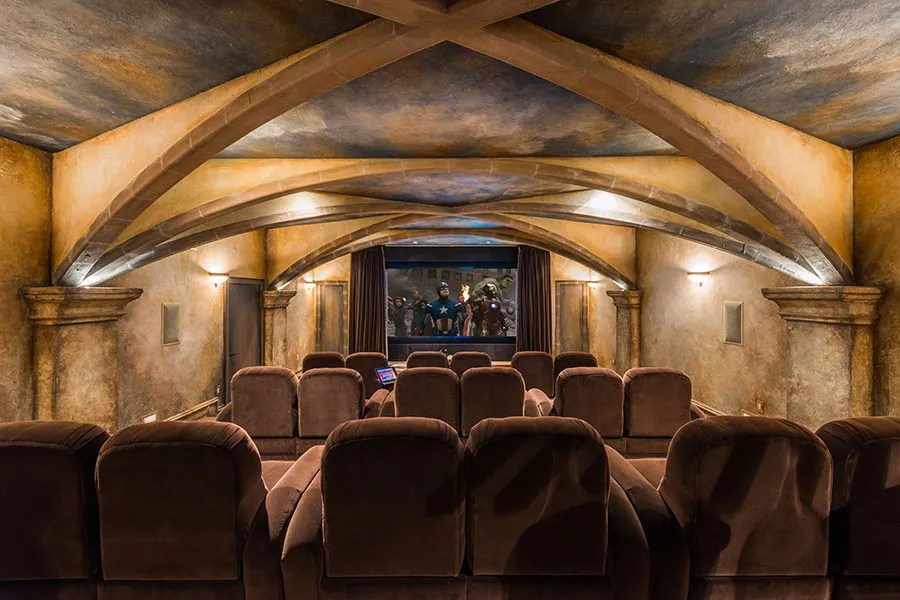 Among other amenities, the home offers a private theater (shown) with dramatic vaulted ceilings, a large fitness center, and an underground ballroom with Brazilian cherry flooring and a commercial-grade kitchen.