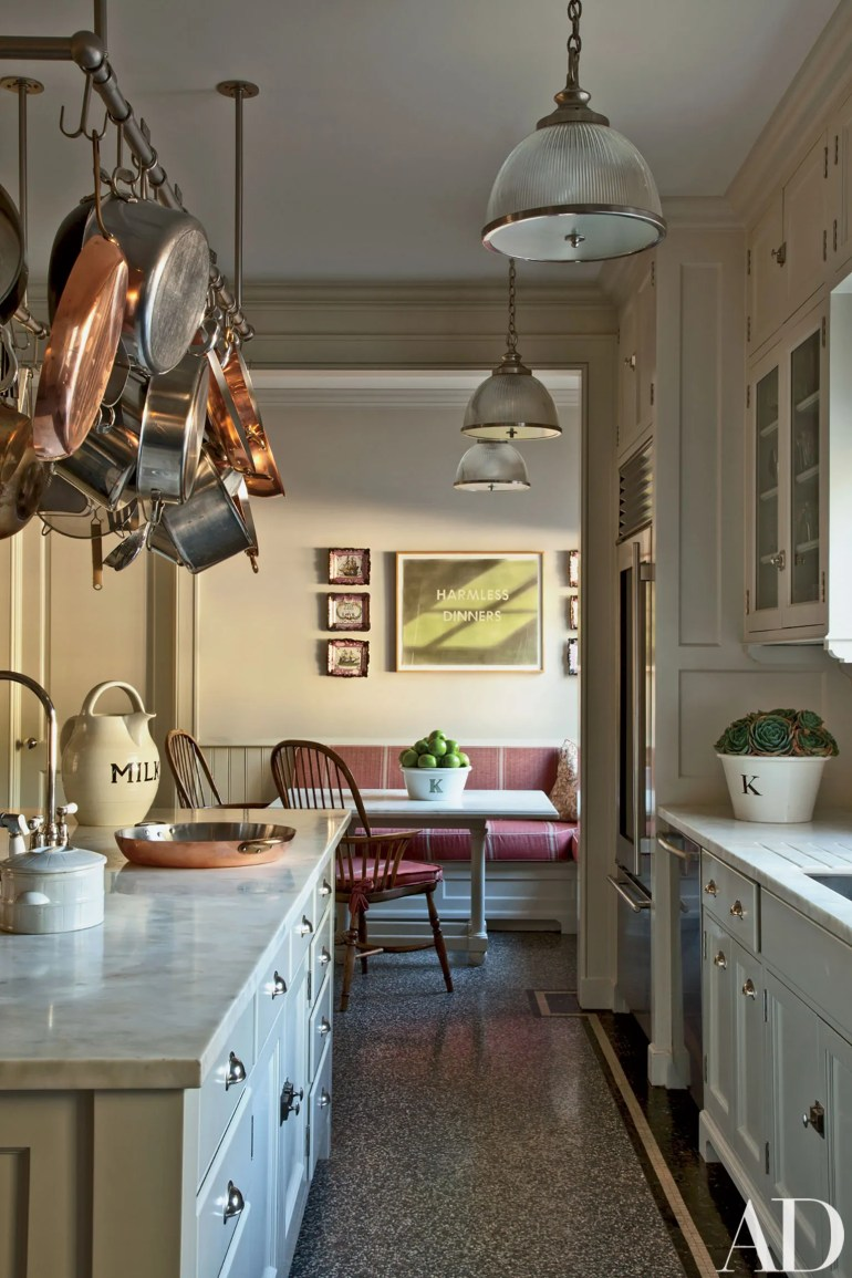 The kitchen's pot rack and pendant lights all by AnnMorris Antiques are installed over counters of Calacatta Sponda marble