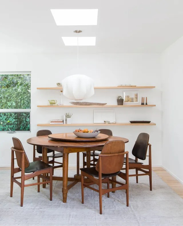 A vintage table from Nickey Kehoe is surrounded by Swedish rosewood-and-leather seating found on Chairish in the dining area. They kept the existing cloud-like pendant light and added a rug by Woven.