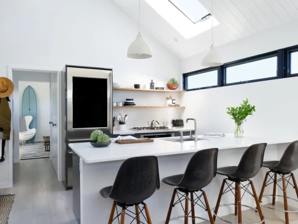 Designer Alicia Murphy went with black Modernica counter stools and heavy cement pendants from Decode for a clean, modern look in the kitchen of her Montauk, New York, trailer-turned-surf-shack. She wanted a constrained black-and-white look for the interior of the space, from the kitchen windows to the striped area rug you can see in the master bedroom.