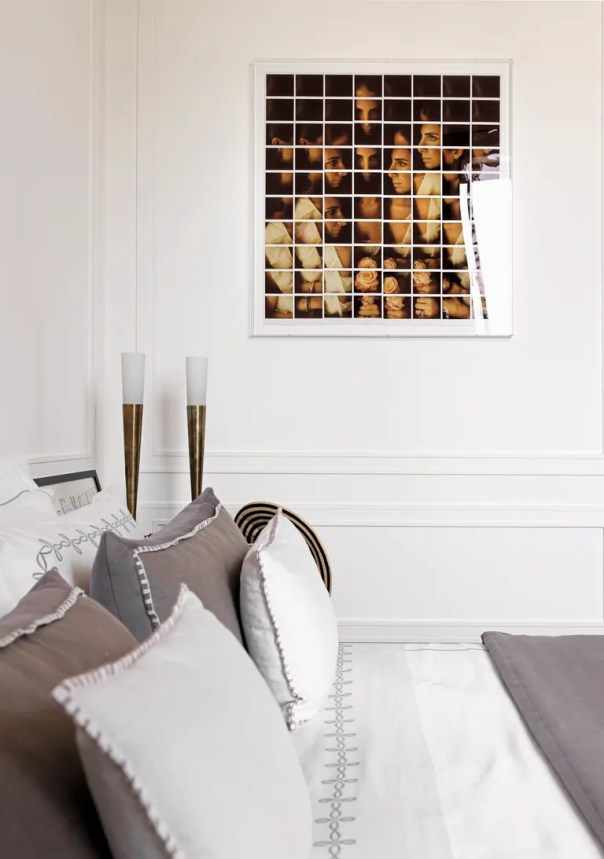 In this home in the Porta Romana neighborhood of Milan, a glimpse into a bedroom shows gray-and-white bedding and a photographic artwork.