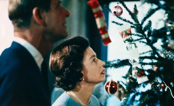 (Original Caption) Christmas at Windsor Castle is shown here with Queen Elizabeth II and Prince Philip shown putting finishing touches to Christmas tree, in a photo made recently during the filming of the joint ITV-BBC film documentary, The Royal Family.