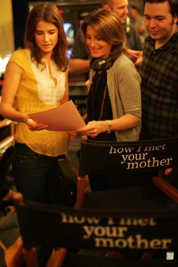 """Director Pam Fryman (center) goes over script with actress Cobie Smulders (left) as Carter Bays (right) looks on on the set of """"How I Met Your Mother"""" on Friday September 26, 2008. Fryman has worked on many of the top sitcoms and is at the helm of CBS's """"How I Met Your Mother"""" which she shoots in a hybrid filming style with multiple cameras without a studio audience. (Photo by Bob Chamberlin/Los Angeles Times via Getty Images)"""