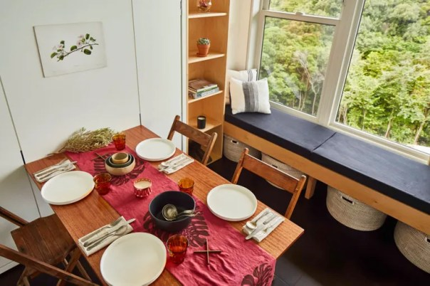 A dining table set for a meal next to a window bench.