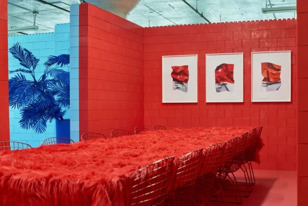 red room featuring three artworks of crumpled pantone swatches, with long red table