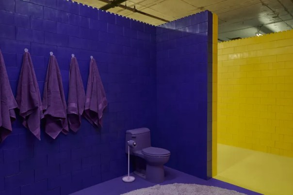 purple room with purple toilet and towels next to all yellow room