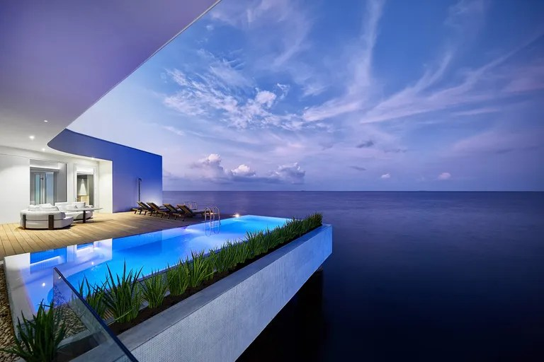 a villa and deck and infinity pool overlooking the ocean in the evening