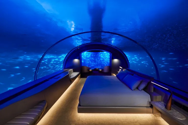 a bedroom covered in glass with fish swimming around it