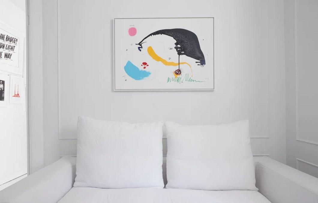 A white sofa below a colorful artwork