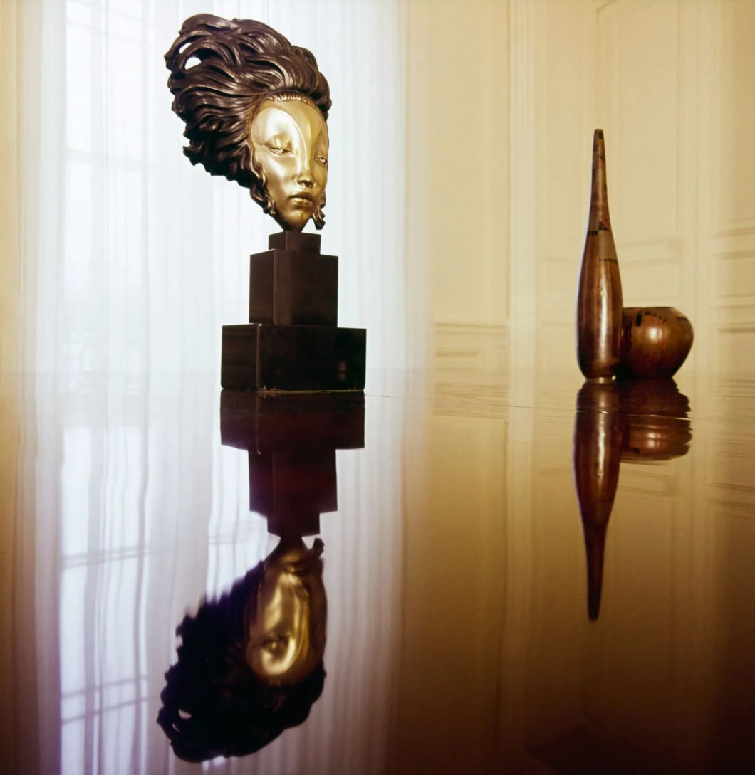 pA bronze mask by Alexandre Kelety and two bronze vases by Jean Dunand sit on a lacquered mahogany table also designed...