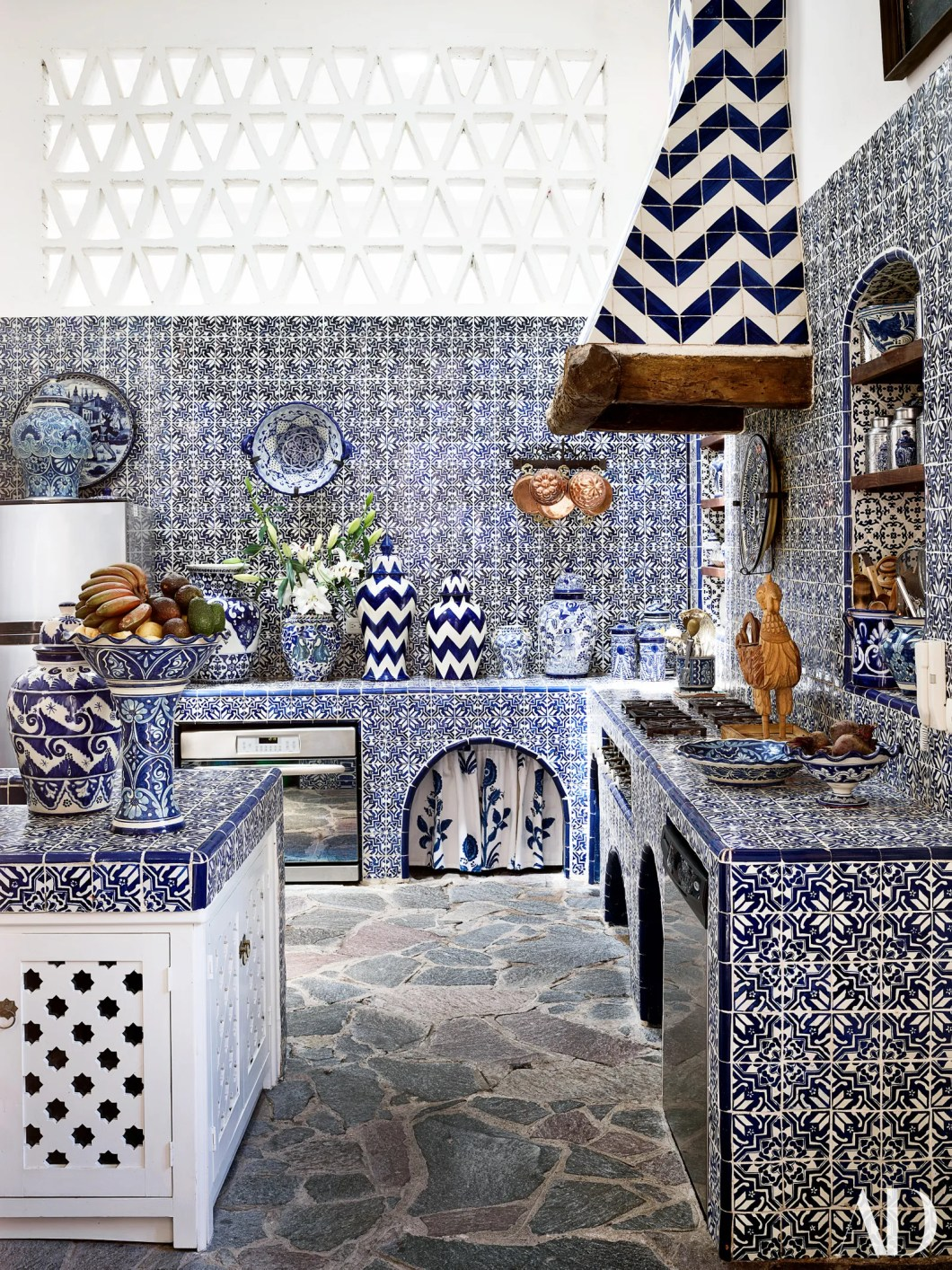 Custom tiles by Nussbaumer from Ceylon et Cie cover the kitchen. Mix of vintage and new jars.