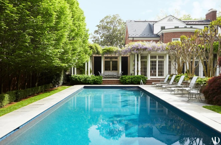 a brick house with a pool behind it