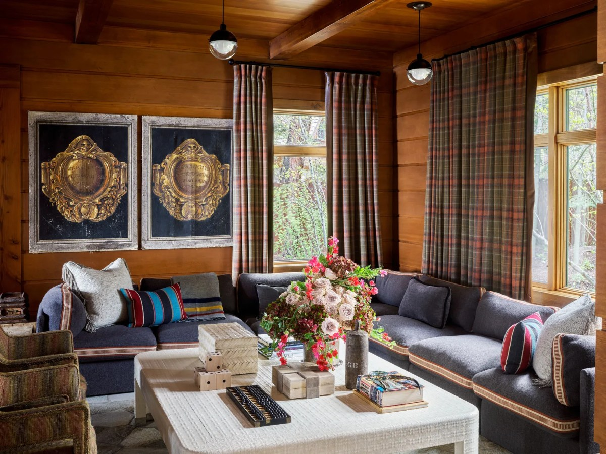 A woodclad family room with plaid curtains.