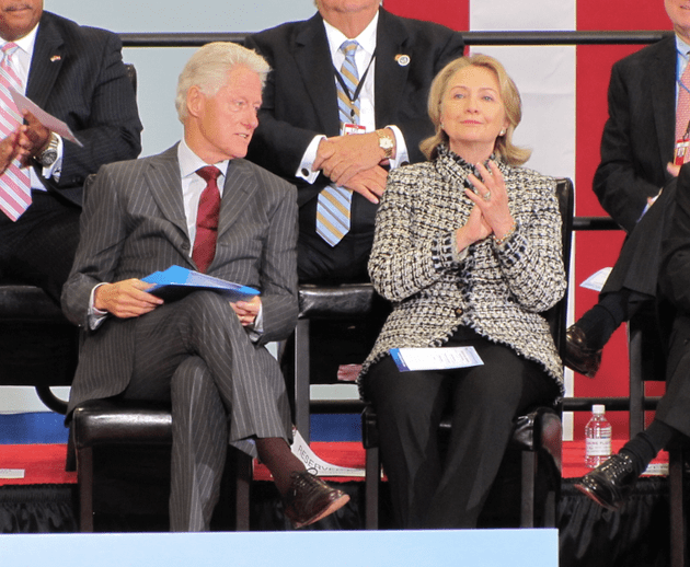 bill-and-hillary-clinton-sit-on-stage-during-a-dedication-ceremony-for-the-little-rock-airport-named-after-them