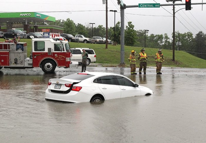 The Sentinel-Record/Richard Rasmussen STANDING BY: Emergency crews stand by the Files Road intersection on Central Avenue, where several vehicles flooded after motorists attempted to negotiate the flood waters.