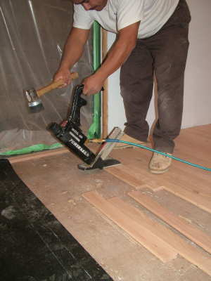 This air-powered nailer drives special nails through the tongue of the hardwood flooring. PHOTO CREDIT: Tim Carter