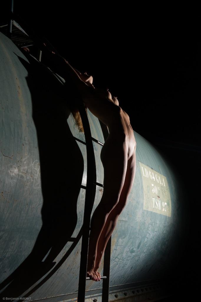 Séance photo nu en extérieur femme montée sur une citerne de nuit