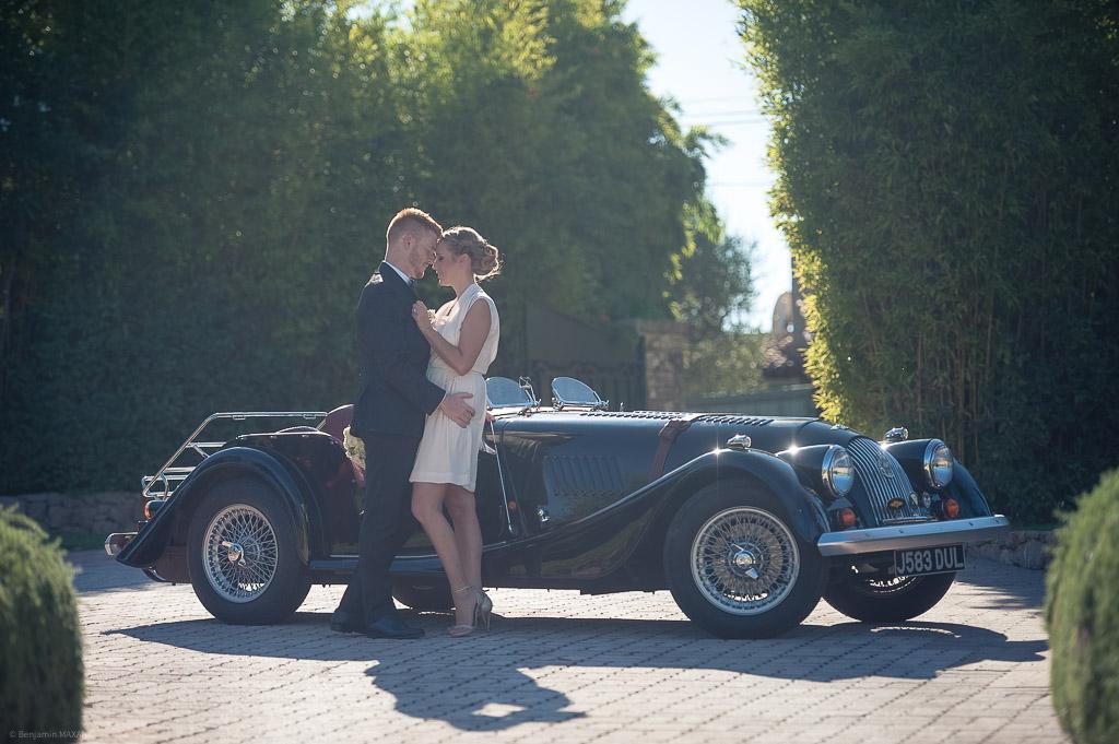 Les jeunes mariés devant la voiture de collection