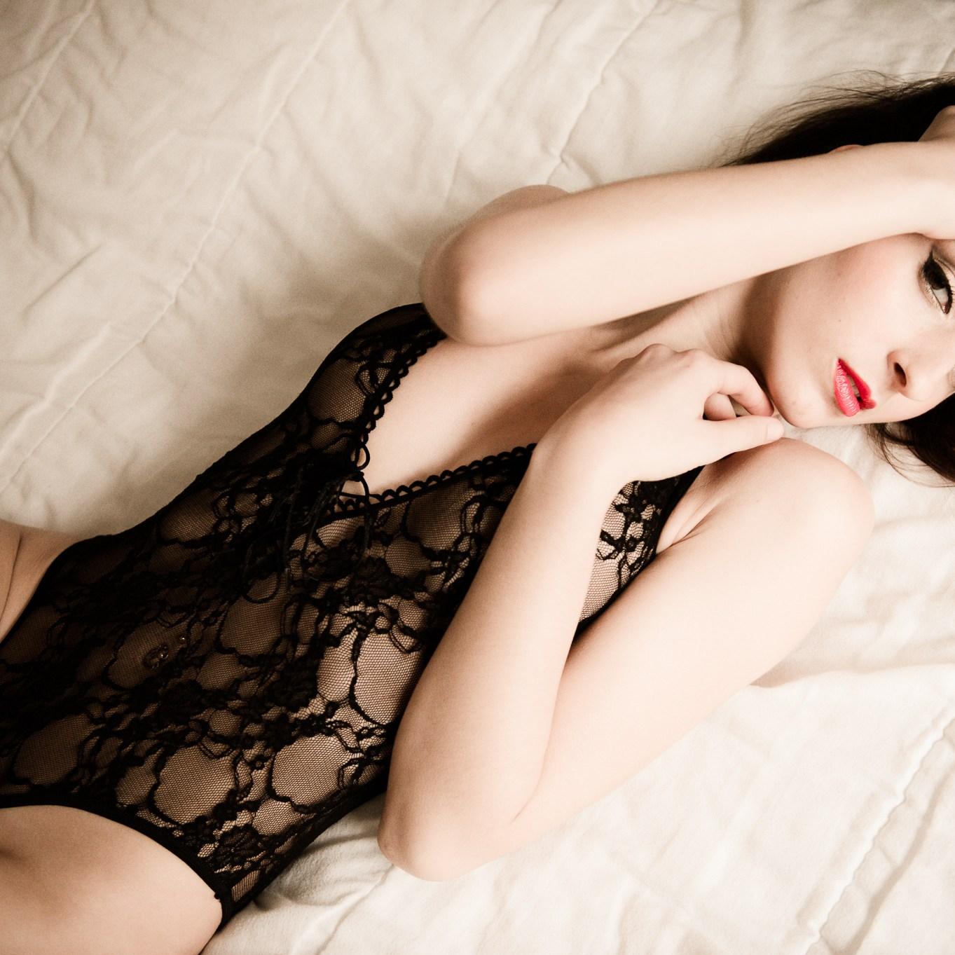 Séance photo boudoir avec Marie allongée sur le lit et portant un body Noir