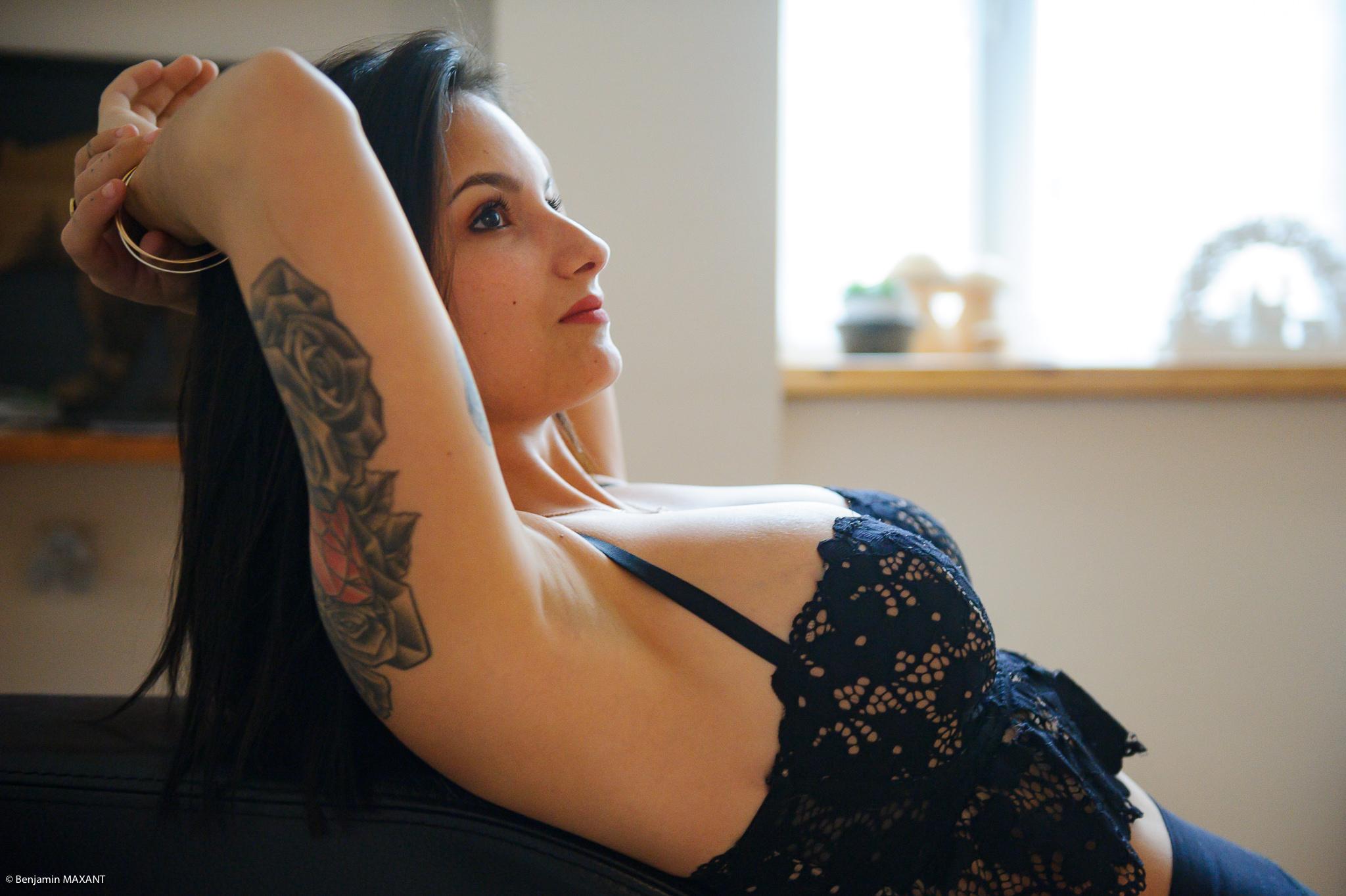 Séance photo boudoir au lingerie noire alongée sur canapé