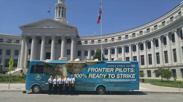 Frontier Airline pilots stand outside the mobile strike center at the Denver City and County Building.