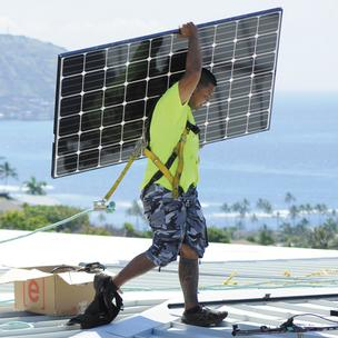 Aaron Paahana, a photovoltaic installer for Hawaii Energy Connection, carries PV panels on a Honolulu rooftop in this file photo. Aiea-based Hawaii Energy Connection had the second-largest number of permits pulled in July, after Utah-based Vivint Solar.
