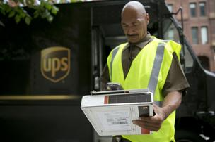 A United Parcel Service Inc. (UPS) employee scans a package while making a delivery.