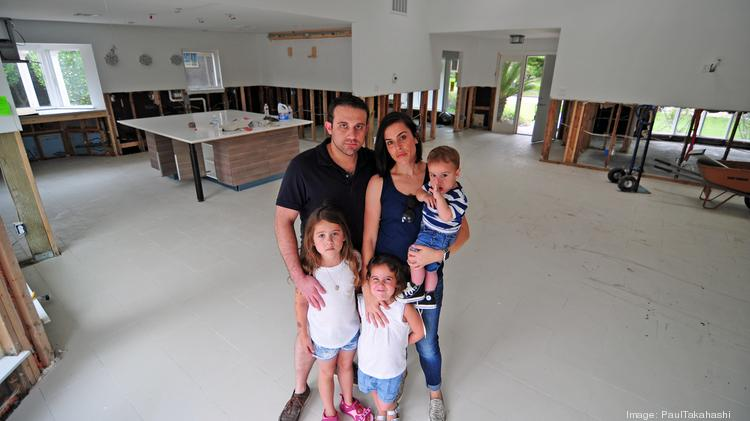 Brett and Nomi Solomon and their three children, stand in the middle of their living room after two floods in less than a year flooded their Meyerland home.