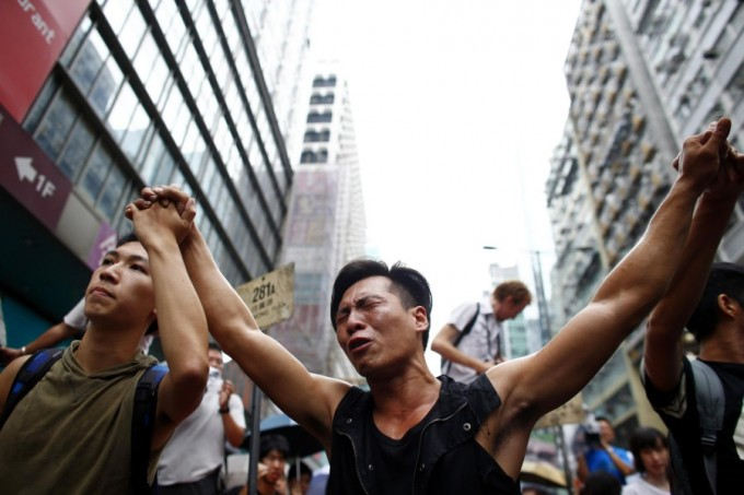 A pro-democracy protester cries after a scuffle with anti-Occupy Central protesters as they try to remove a barricade at a main street at Hong Kong's Mongkok shopping district October 4, 2014. [Reuters]