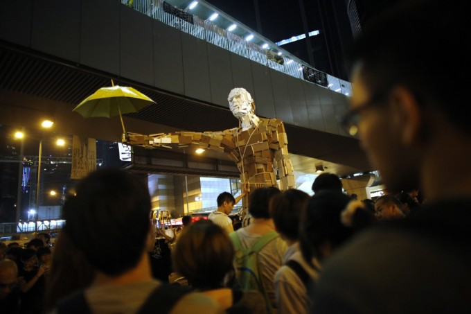 Protesters install a statue with a yellow umbrella as other demonstrators block the main street to the financial Central district outside of the government headquarters building in Hong Kong October 5, 2014. [Reuters]