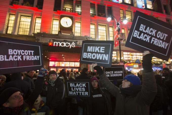 Protesters hold signs aloft outside Macy's before the kick off of Black Friday sales in New York November 27, 2014. REUTERS/ANDREW KELLY