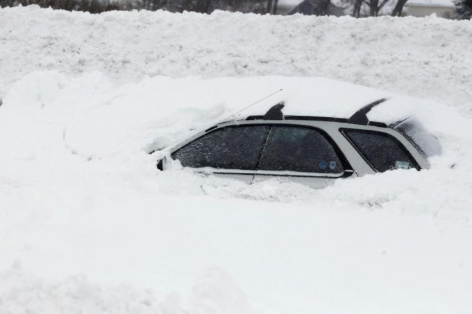 A vehicle is shown submerged in snow on interstate I-190 in West Seneca. SHARON CANTILLON/BUFFALO NEWS/POOL/REUTERS