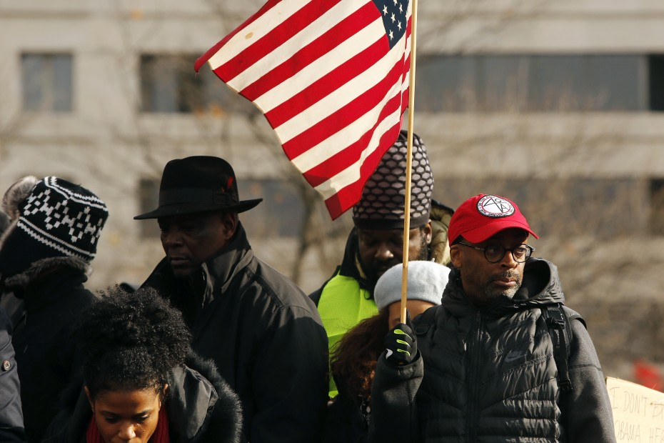 Film director Spike Lee (R) holds a flag during a rally before the national Justice For All march against police violence, in Washington December 13, 2014.   REUTERS/Jonathan Ernst